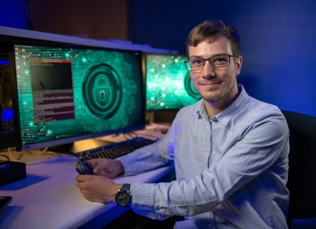 a man wearing glasses sits at dual monitors and looks directly at the camera