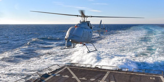helicopter landing on back of ship in ocean