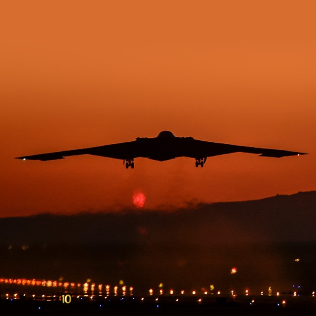 b-2 bomber flying into a red sky at sunset