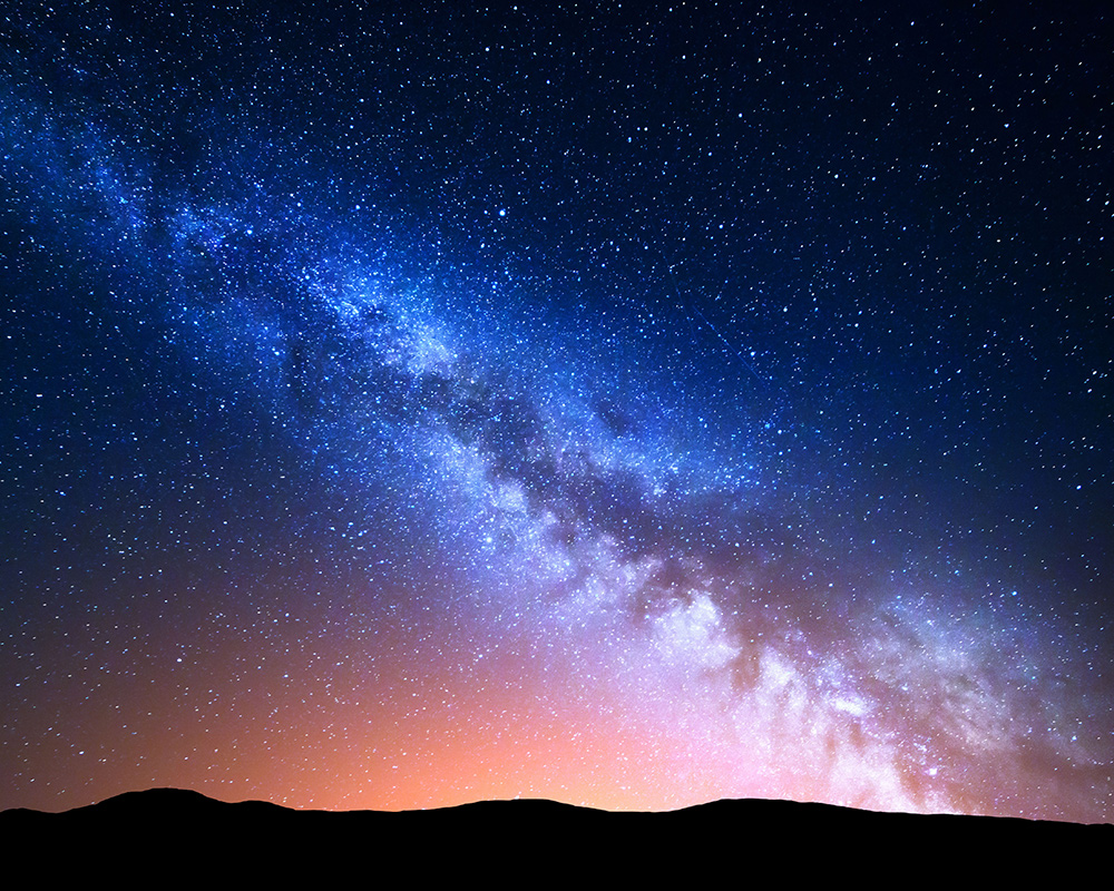 milky way and silhouette of mountains