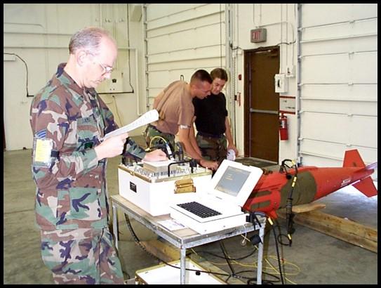Service members in uniform work around desk of equipment