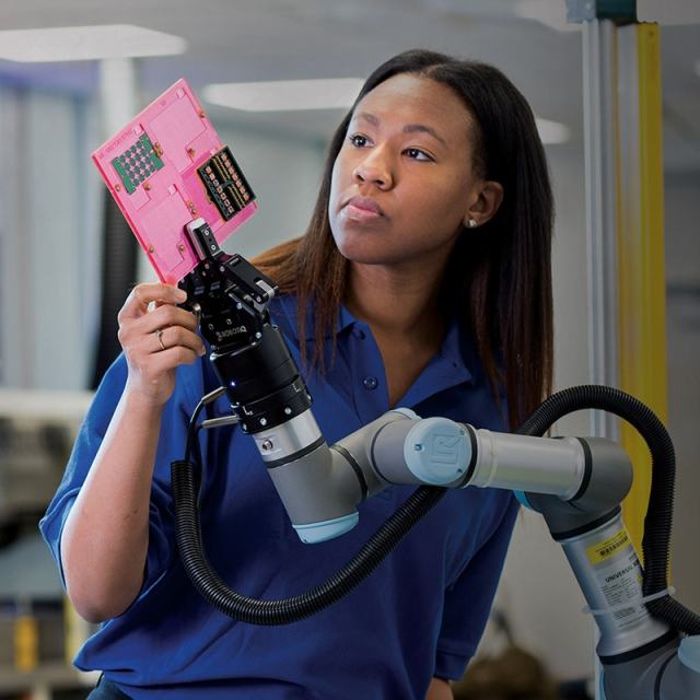 black woman working with robot arm holding microchip