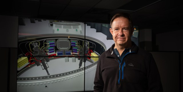 a white man stands in front of a computerized image