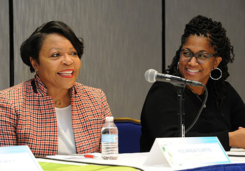 Two Black women speaking at a table in front of a microphone