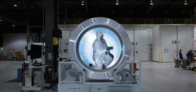 Human crouching inside of rocket machinery parts in factory setting