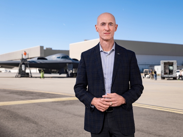 Man dressed in business wear standing in front of military aircraft