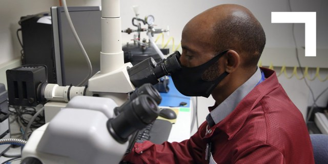 a man in a maroon lab coat looks into a telescope