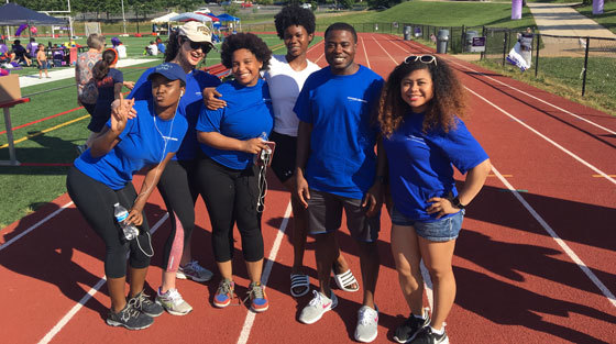 Six people stand on an athletic track and smile for the camera at a Relay for Life event