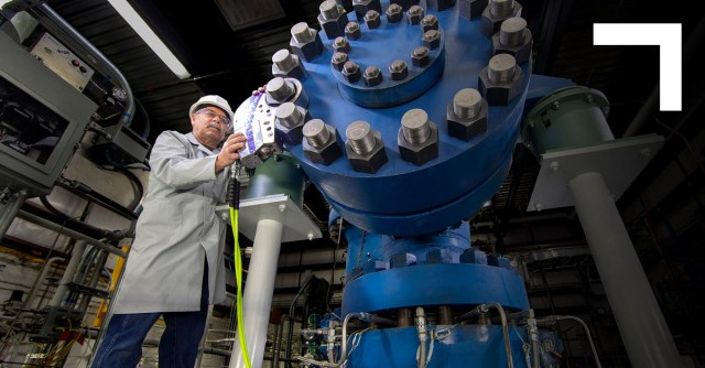 man in front of very large blue gear