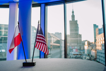 Poland and US flags sitting on desk.