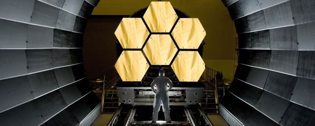 Man standing in a tunnel looking at the gold hexagon mirrors of the James Webb Space Telescope