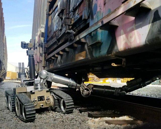 hazardous duty robotic vehicle with arm extended under a train car