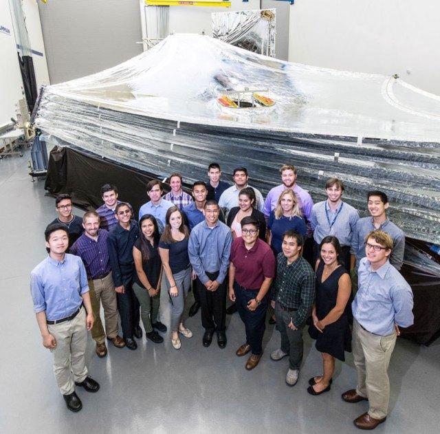 A group of Northrop Grumman interns stand next to a sunshield