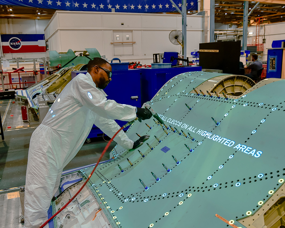 man working on military aircraft in manufacturing facility