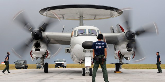man standing in front of military plane with large propellers