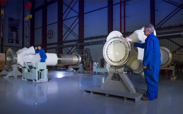 two men in blue coats work on rocket