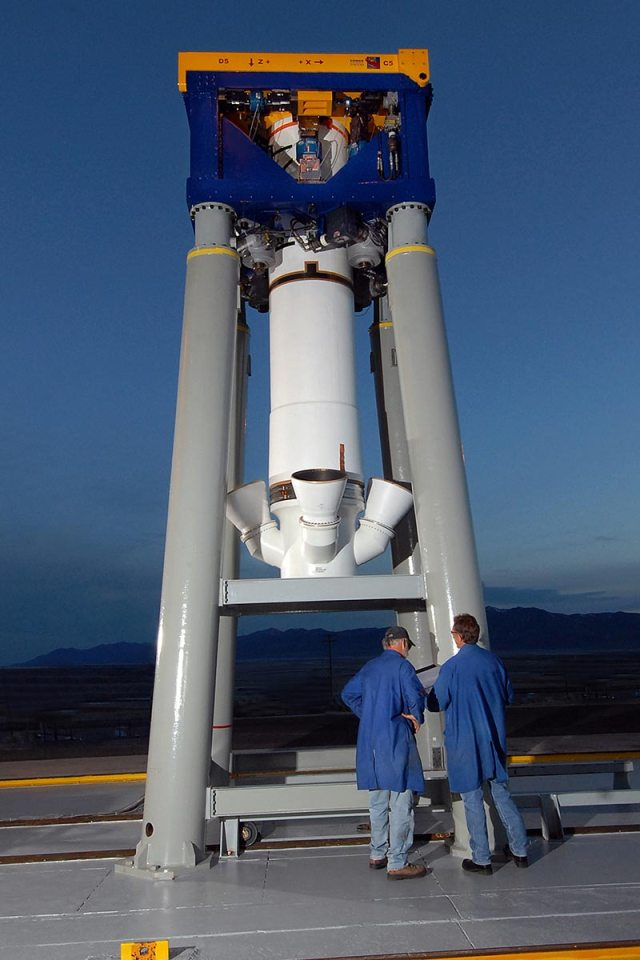 two men in blue coats stand in front of rocket test motor