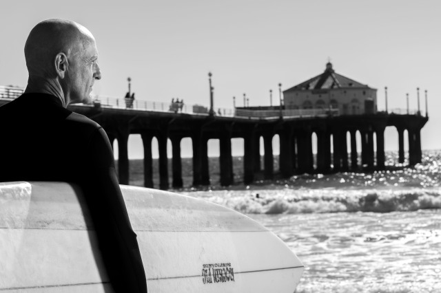 Older Caucasian man in wetsuit holds surfbboard at the beach