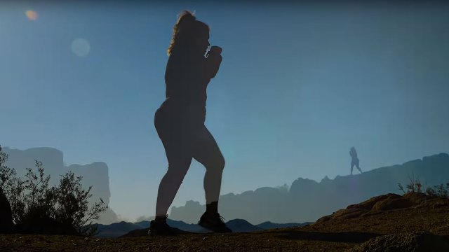 woman shadow boxing on mountain trail