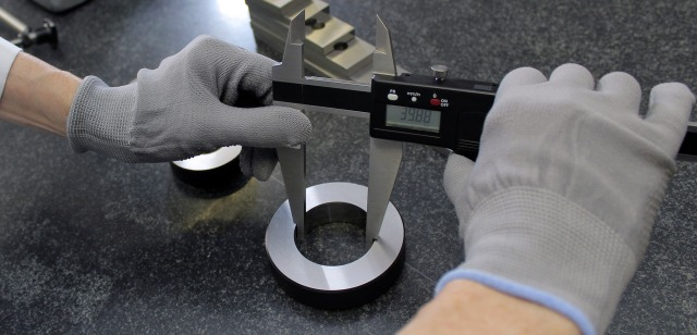 Hands operating measuring tools in a manufacturing environment.