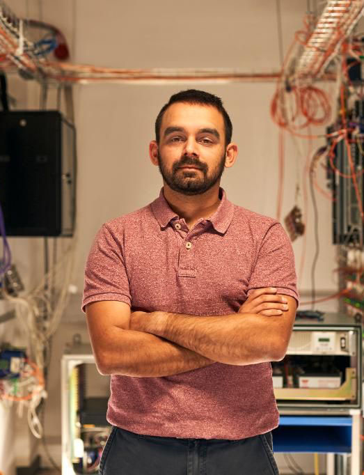 man standing with arms folded in a data room with computers and wires in the background