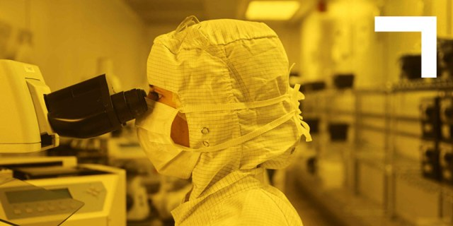 woman in clean room looking through microscope
