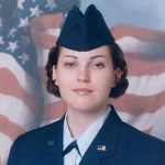 female soldier in front of flag