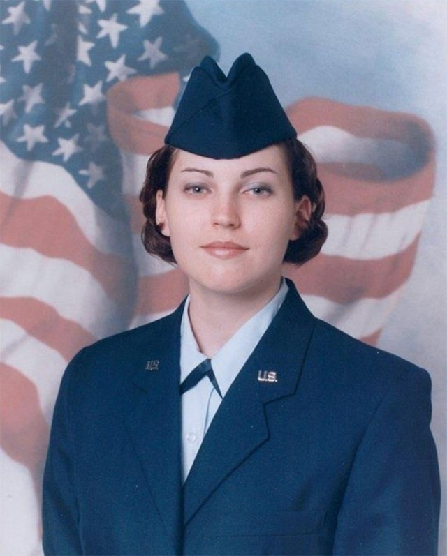 female soldier in uniform in front of flag