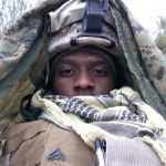 African American soldier in front of flag
